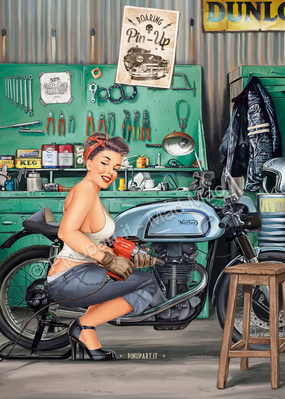A mechanic pin-up in the garage tuning a 1953 Norton classic cafe racer